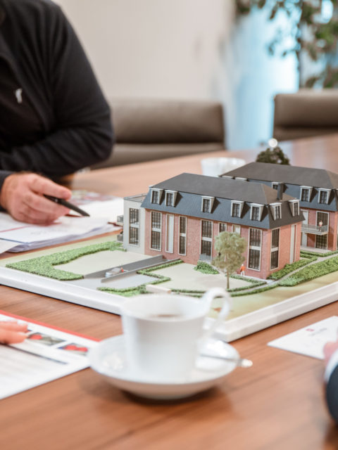 Sallier Bauträger Besprechung Bauprojekte mithilfe eines Modells mit zwei Häusern