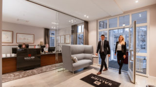 Eingang Immobilienbüro Sallier Immobilien zwei Menschen betreten den Empfangsbereich